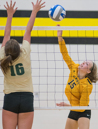 Mankato East's Sarah Strom (15) hits the ball over Rochester Mayo's Kelly Klees in Tuesday's game. East lost to Mayo in four sets. Photo by Jackson Forderer