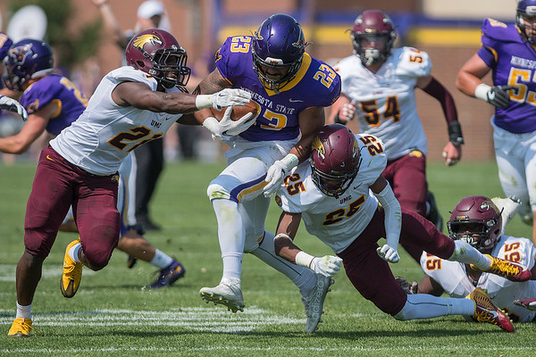 Minnesota State's Nate Gunn (23) runs into the University of Minnesota Crookston's secondary, Donovan Baker (21) and Will Cole (25), during a big run against the Golden Eagles. MSU overcame a slow start to rout Crookston 56-19. Photo by Jackson Forderer