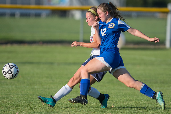 Amelia Carlson of St. Peter takes a shot on goal early in the second half while being defended by Alexis Breuer in Thursday's match. St. Peter scored the game's lone goal to win 1-0. Photo by Jackson Forderer