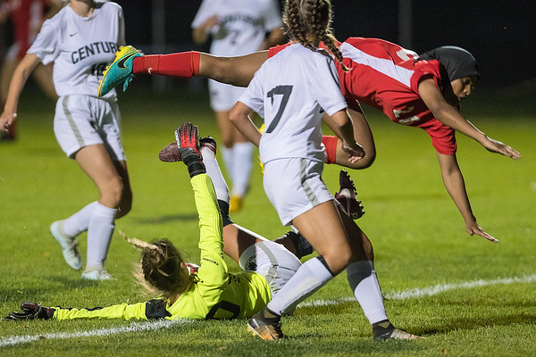 Monroe McMahon of Mankato West gets airborne while going for the ball but also trying to avoid a major collision with Rochester Century goalie Sydney Sukalski. Photo by Jackson Forderer