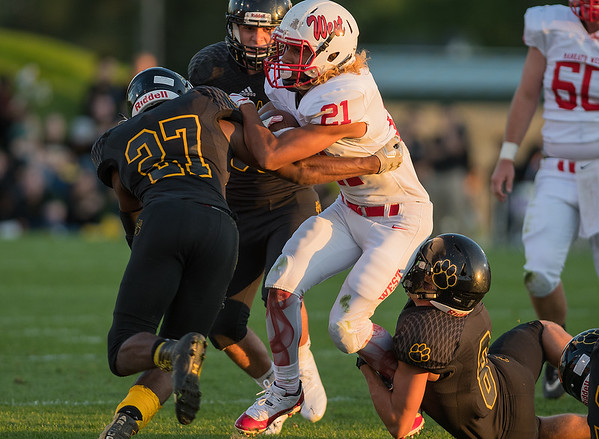 Mankato West's Melik Davis tries to break through Mankato East's Leslie Miller (27) and Isaac Turner in the first quarter. The Scarlets won 48-20 to take home the jug for the 13th consecutive year. Photo by Jackson Forderer