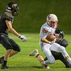 Jacob Eggert of Mankato East slows down Mankato West's Max Goertzen (28) enough for his teammates to finish the tackle along the sidelines during Friday's game. Photo by Jackson Forderer