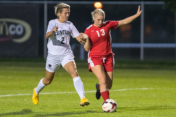 Mankato West's Kristen Rasmussen is pressured by Rochester Century's Nicole Powell as Rasmussen dribbled toward the goal in the second half of Tuesday's game. The Scarlets won the game 3-0 over the Panthers. Photo by Jackson Forderer