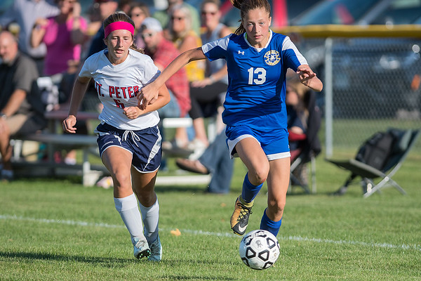Mankato Loyola/LCWM/St. Clair/Madelia's Julia Schumacher (13) gets past St. Peter's Nicole Schilling in the first half of play in Thursday's soccer match. St. Peter won the match 1-0 in a Big South conference matchup. Photo by Jackson Forderer
