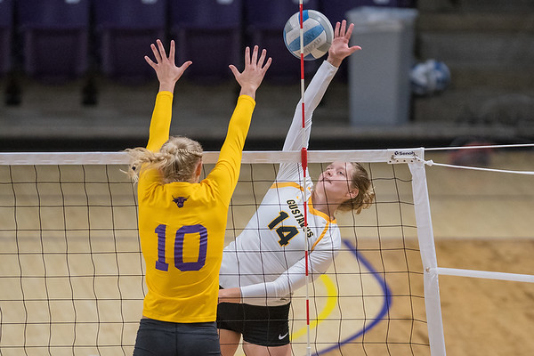 Gustavus' Hanna Albers hits a spike over the outreached arms of Minnesota State's Morgan Olson. Photo by Jackson Forderer