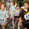 Preston Daley, at right, stretches out with a group of young runners before their race at the West End 3K  on Pearl Street on Thursday, July 22, 2010, in downtown Boulder.<br /> Jeremy Papasso/ Camer