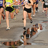 The women's elite racers are reflected through a puddle at the West End 3K race on Pearl Street on Thursday, July 22, 2010, in downtown Boulder. <br /> Jeremy Papasso/ Camera
