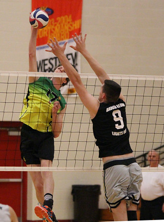 STEPHEN BROOKS | THE GOSHEN NEWS<br /> Matt Harpenau of Team Pineapple, left, leaps for a spike while Noah Mader of Team Lights Out, right, attempts the block during Saturday's exhibition charity game at Westview High School. Team Pineapple, led by four-time Olympian and gold medalist Lloy Ball, and Team Lights Out, led by USAV national champion Harshil Thaker, played an exhibition match with all proceeds going to Haven of Hope Ministries.
