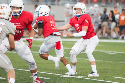 Leander senior Kyle Irlbeck passes the ball off to senior Jai Garcia against Westwood Friday at Bible Stadium.
