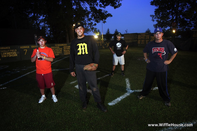 "Shawn Brown (cq) (30) (Left Center) of Burton stands with some of his whiffle ball teammates (L-R) Stephon Drzewicki (cq) (18) of Bay City, Alan Garcia (cq) (30) of Essexville, and Andy Taylor (cq) (23) of Flint at ""Brown's Field"" in Burton on Wednesday evening. The whiffle ball stadium is in the backyard at Brown's house and was  erected for the first time in 1984.  The stadium is torn down in the winter and put up in every summer."