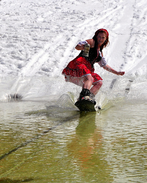 "Dayne Callum, of Salem MA, and the Brettl-Hupfer Ski Club, of North Conway, NH, attempted to cross a pond on her snowboard while dressed as an Oktoberfest waitress, during Wildcat Mountain Ski Area's annual ""Wet Ditch Skim Contest, held Saturday, April 3rd, 2010. Skiers & riders attempted to carry as much speed as possible to skim across a water-filled ditch, at the base of the Pinkham Notch ski area, in Jackson, NH."