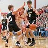 Churubusco Eagles guard Gage Kelly (10) and Churubusco Eagles forward Tim Knepple (31) defend  Westview Warriors forward Charlie Yoder (5) during the Friday night game at Westview High School in Topeka.