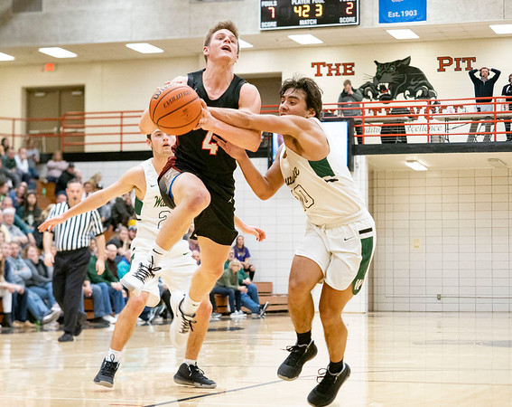 Wawasee Warriors guard Ethan Carey (20) defends NorthWood Panthers guard Brock Flickeringer (4) during the NorthWood 3A Sectional Championship game Saturday evening at NorthWood High School.