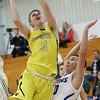 JAY YOUNG | THE GOSHEN NEWS<br /> Fairfield junior Luke Stephens (11) finds a path to the hoop around Bethany senior Zane Zmudzinski (10) during their game Tuesday evening in Goshen.