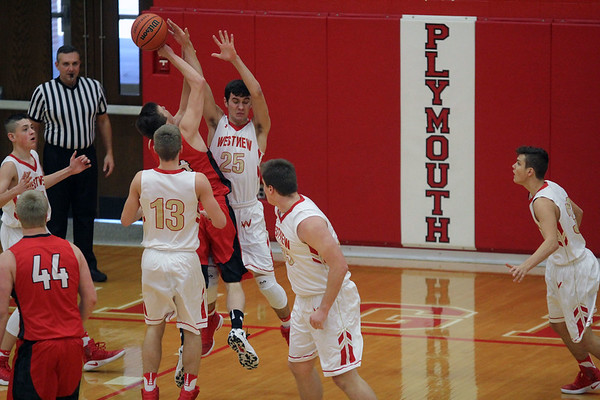 GREG KEIM | THE GOSHEN NEWS<br /> Junior Logan Kruse of the DeKalb Barons drives to the basket while being defended by No. 13 sophomore Elijah Hales and No. 25 Cody Collyer of the Westview Warriors Tuesday in the Plymouth Shootout. Westview was a 59-41 winner.