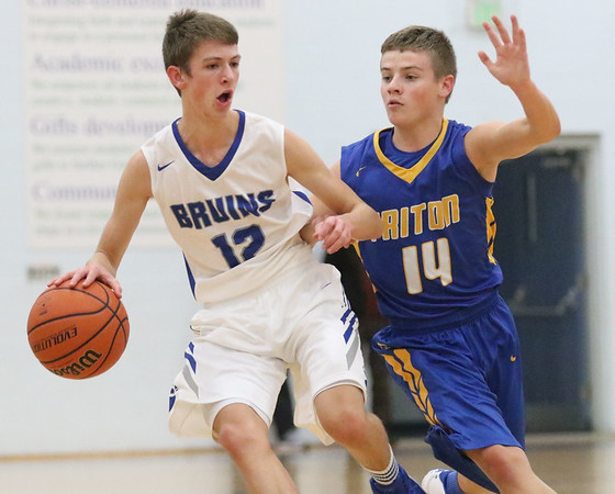 JAY YOUNG | THE GOSHEN NEWS<br /> Bethany Christian junior Kory Kern (12) is hounded by Triton sophomore Beau Hepler (14) as he brings the ball up the court to set the Bruins' offense during their game Tuesday night at Bethany.
