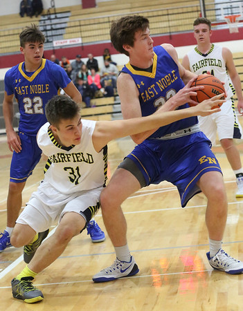 JAY YOUNG   THE GOSHEN NEWS<br /> East Noble junior Drew Devers (33) pulls a rebound away from Fairfield senior Zach Munn (31) during their game in the 2016 Holiday Basketball Tournament hosted by Goshen High.