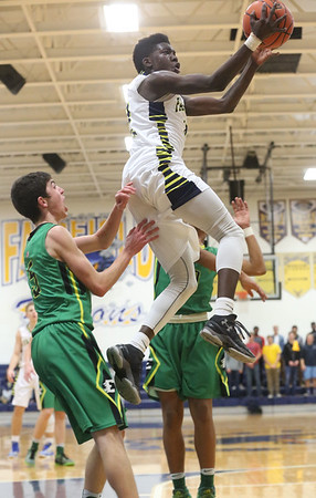 JAY YOUNG | THE GOSHEN NEWS<br /> Fairfield junior Tyshawn Knight soars between Eastside defenders Jordan Yoder, left, and Aaron Dean  during their quarterfinal game in the NECC Basketball Tournament Wednesday night at Fairfield.