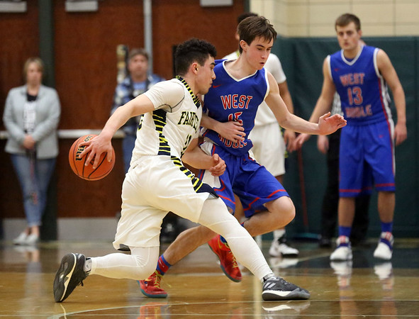 JAY YOUNG | THE GOSHEN NEWS<br /> West Noble senior Brady Willard crosses the ball over behind his back while trying to escape the defensive pressure by West Noble senior Walker Donley (15) during their 3A sectional championship game on Saturday night.