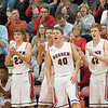 JAY YOUNG | THE GOSHEN NEWS<br /> Goshen bench players and fans cheer a Redhawks' three pointer during the Redhawks' game against Marian on Tuesday evening at GHS.