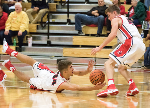 JAY YOUNG   THE GOSHEN NEWS<br /> Goshen's Eliot Nafziger (34) dives on the floor to save the ball to teammate Bryant Robinson (44) their game against Marian on Tuesday evening at GHS.