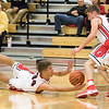 JAY YOUNG | THE GOSHEN NEWS<br /> Goshen's Eliot Nafziger (34) dives on the floor to save the ball to teammate Bryant Robinson (44) their game against Marian on Tuesday evening at GHS.