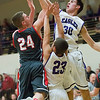 JAY YOUNG | THE GOSHEN NEWS<br /> Elkhart Christian Academy senior Jonah Jara Wallick (30) sends back a shot put up by Goshen High senior Mitchell Walters (24) while sophomore Ryan Charles (23) defends during their game Tuesday night in Elkhart.