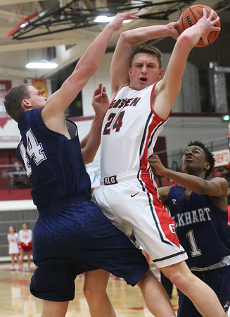 JAY YOUNG   THE GOSHEN NEWS<br /> Goshen High senior Mitchell Walters (24) pulls down a rebound between Elkhart Central's Michael Boone and Amarion Bartlett (1) during their game in the 2016 Holiday Basketball Tournament hosted by Goshen High.