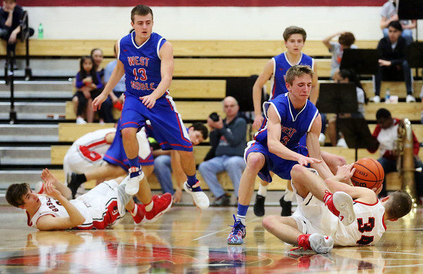 JAY YOUNG   THE GOSHEN NEWS<br /> Goshen High senior Eliot Nafziger  (34) dives to the floor to pick up a loose ball in front of West Noble sophomore Trevor Franklin (23) during their game Tuesday night at Goshen High School.