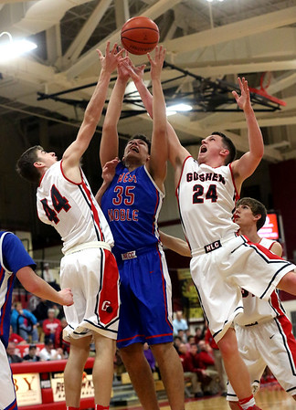 JAY YOUNG | THE GOSHEN NEWS Goshen High's Bryant Robinson (44) and Mitchell Walters (24) fight for a rebound with West Noble senior Larry Nickolson (35) during their game Tuesday night at Goshen High School.