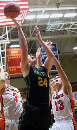 JAY YOUNG | THE GOSHEN NEWS<br /> Northridge junior Nick Yoder (24) forces up a shot between Warsaw defenders Jack Rhoades (13) and Nolan Groninger (3) during their 4A sectional tournament game Wednesday night at Northside Gym in Elkhart.