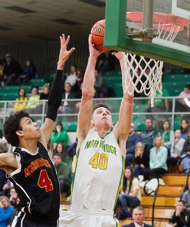 SAM HOUSEHOLDER   THE GOSHEN NEWS<br /> Northridge senior Nate Ritchie dunks against Elkhart Memorial junior Dimitri Giger Wednesday during the game.