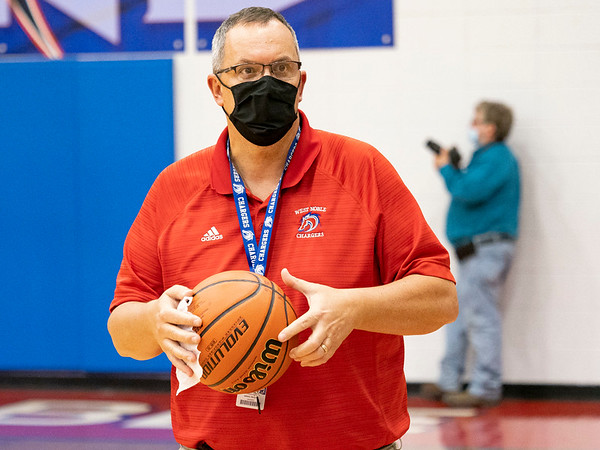 West Noble Chargers athletic director Tom Schermerhorm sanitizes the game ball  at half time during Thursday's game at West Noble High School in Ligonier.