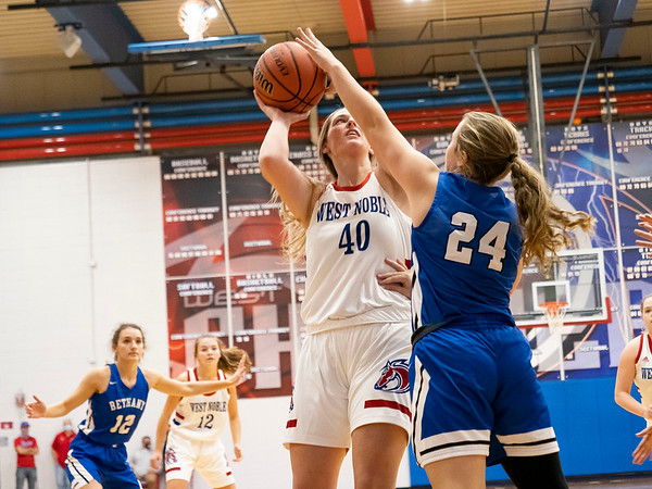 West Noble Chargers senior Nichelle Phares (40) goes up for a basket against Bethany Christian Bruins freshman Mariah Stoltzfus (24) during Thursday's game at West Noble High School in Ligonier.