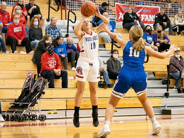 West Noble Chargers senior Erin Shoemaker (10) shoots a basket against Bethany Christian Bruins senior Rilynn Kaufmann (10) during Thursday's game at West Noble High School in Ligonier.