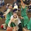 JAY YOUNG | THE GOSHEN NEWS<br /> Fairfield junior Jenean Schwartz, center, dribbles out of a double team by Eastside defenders Hannah Yoder, left, and Maddisyn Heffley, right, during their quarterfinal game in the NECC Basketball Tournament Wednesday night at Fairfield.