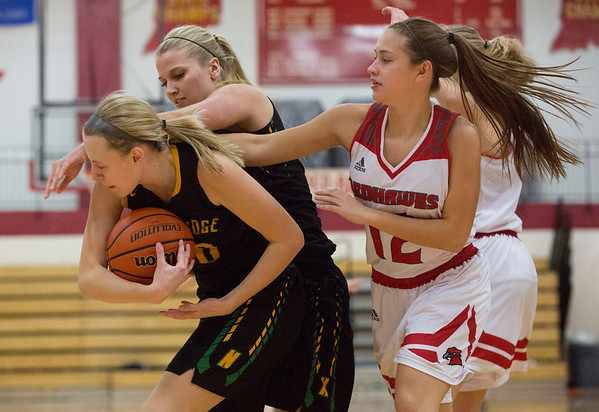 JAY YOUNG   THE GOSHEN NEWS<br /> Northridge junior Brooke McKinley, left, rips a rebound away from teammate Kelsey Brickner, center, and Goshen High senior Jordan Nemeth (12) during the first half of their game Friday night at GHS.