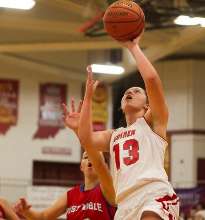 SAM HOUSEHOLDER | THE GOSHEN NEWS<br /> Goshen junior Alyssa Hershberger goes up for a basket past West Noble junior Paige Shearer during the game Tuesday.