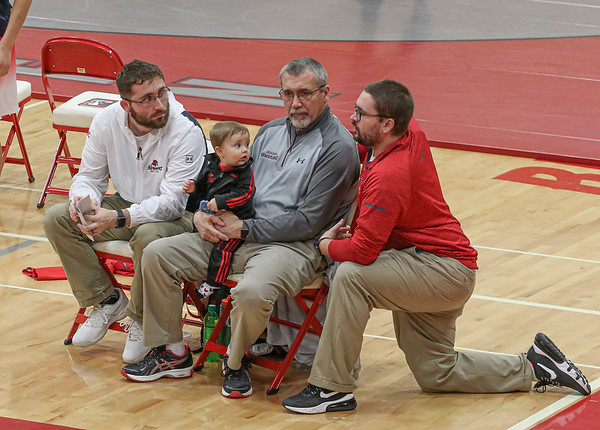 The Pickard family, from left: Travis, Cael, Jim and Troy, discuss strategy during the Goshen Invitational Saturday. Because of the changes made to the schedule, Jim ended up coaching against Troy in a varsity vs. junior varsity match.