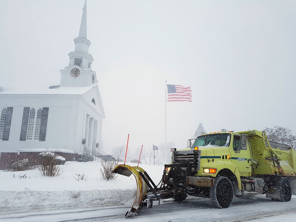 . Plow in Chelmsford Center passes by the First Parish Unitarian Universalist Church during winter storm. (SUN/Julia Malakie)