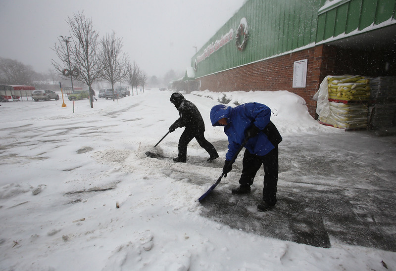 Winter storm features in Billerica. Hippolito Quex of Billerica, right, and Josue Ramos of Lynn, who work for O'Connor Hardware, keep the front clear of snow.  (SUN/Julia Malakie)