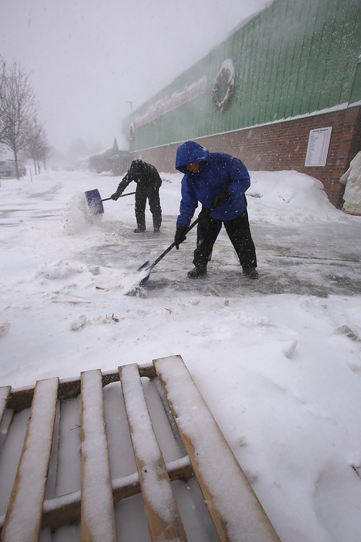 . Winter storm features in Billerica. Hippolito Quex of Billerica, right, and Josue Ramos of Lynn, who work for O\'Connor Hardware, keep the front clear of snow.  (SUN/Julia Malakie)