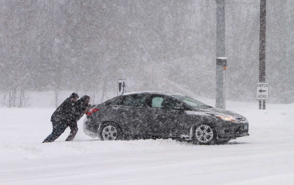 . Winter storm features in Chelmsford. Man from this car, and from the next car coming off the exit from Rt 3 Southbound to Rt 110 in Chelmsford, push the car out of the snow onto Rt 110. (SUN/Julia Malakie)