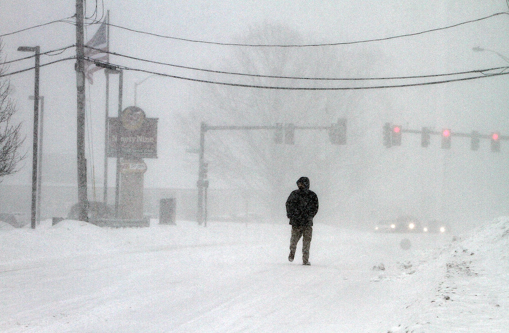 . Winter storm features in Lowell. Nara Chan of Lowell walks home on Rt 110 from Kohl\'s. He\'d just gone to buy his jacket because he had a coupon, and got tired of waiting for the bus home. (SUN/Julia Malakie)