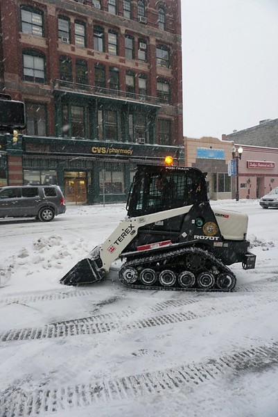 With the storm picking up in intensity, Ed Larkin of the Lowell Department of Public Works keeps downtown sidewalks clear at the intersection of Merrimack and Central Streets. (SUN PHOTO/ Chris Tierney)