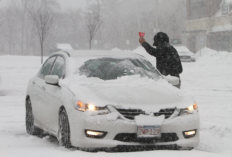 Winter storm features in Chelmsford. William Campos of Tyngsboro clears his car windows after working out at Choice Fitness in Chelmsford Town Center. (SUN/Julia Malakie)