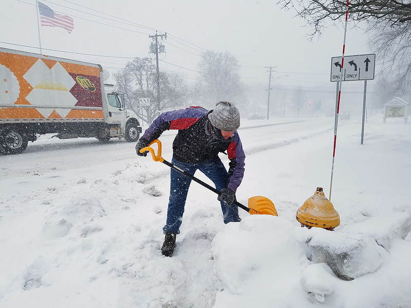 Winter storm features in Billerica. John Marshall of Billerica clears snow from the hydrant in front of the Billerica Public Library. He said he hears on the radio about the need to shovel hydrants, and does the one nearer his house. This one was extra. (SUN/Julia Malakie)
