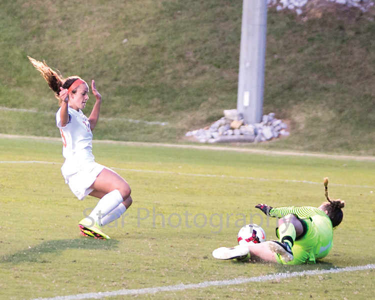 Star Photo/Larry N. Souders<br /> After her shot on goal, Milligan's Ellie Cachiares (23) nearly collides with King goalie Olivia Drake (1) as she slides in for the save.