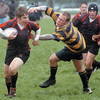 Mark Peck passes by a Wildcat defender during the Ohio Rugby Classic at Lou Berliner Park on Saturday.