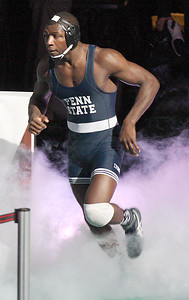Penn State Ed Ruth runs through smoke on his way onto the mat for the 184-pound championship bout on Saturday night. Ruth won his third straight NCAA title. (Tim Tushla/For The Daily Item)